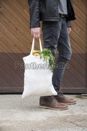 adolescente carregando sacos de compras reutilizaveis