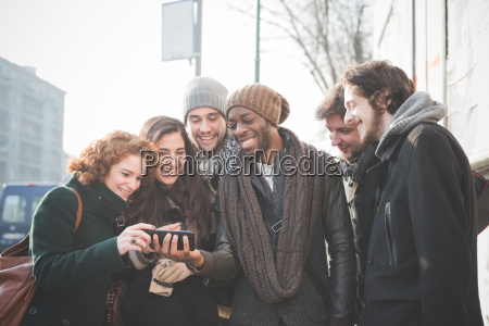 six young adult friends reading smartphone