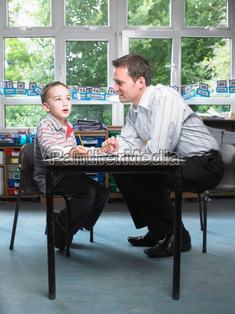 male teacher helping young boy with