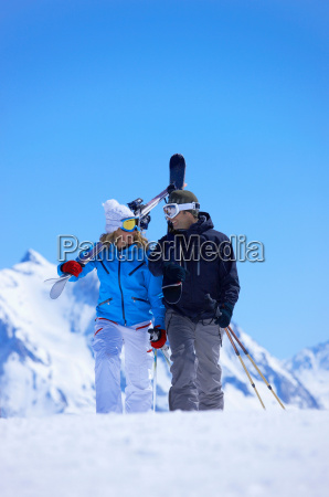 couple walking with skis over shoulder