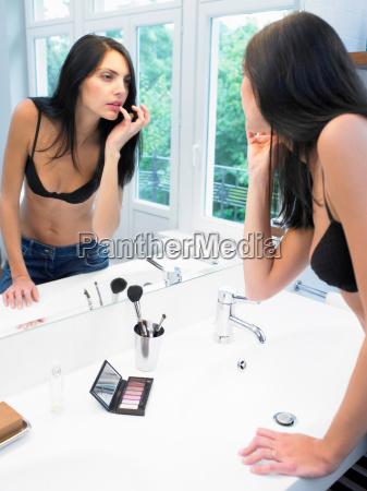 woman applying makeup in bathroom