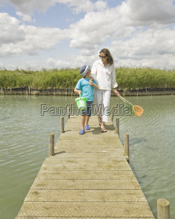 woman and boy walking on jetty