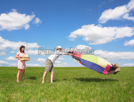young people with picnic in field