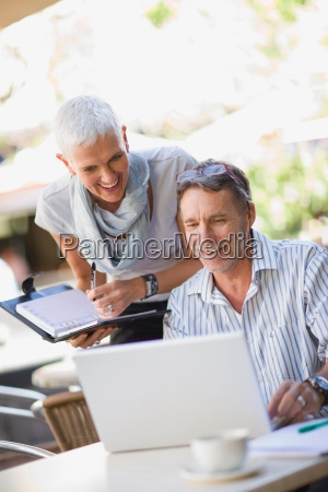 business people using laptop outdoors