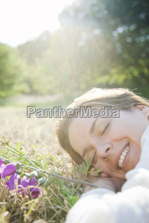woman lying in grass with flowers