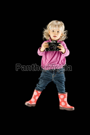 girl and camera against black background