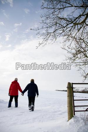 senior couple walking in the snow
