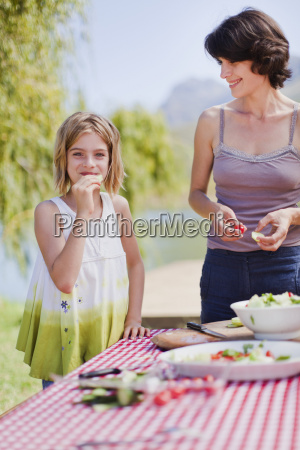 mother and daughter making picnic lunch