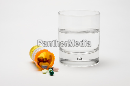 comprimidos e um copo dagua