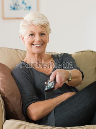 a senior woman watching tv