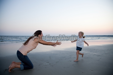 girl running to mother on beach