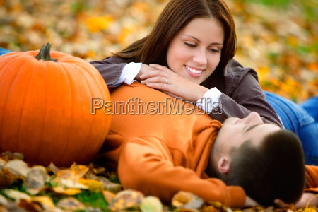 young couple lying on the leaves