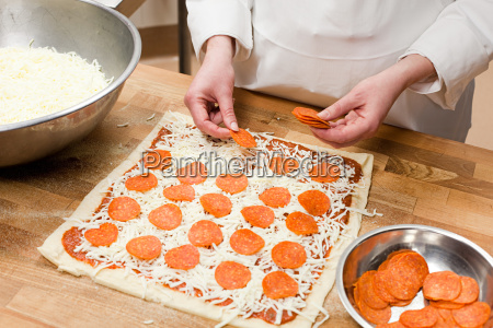 female chef making pizza in commercial
