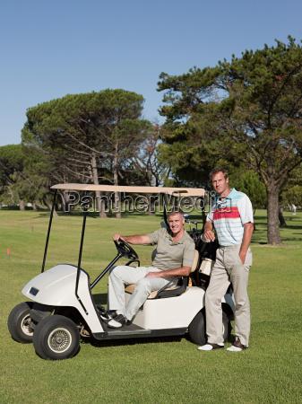 two mature men in golf cart