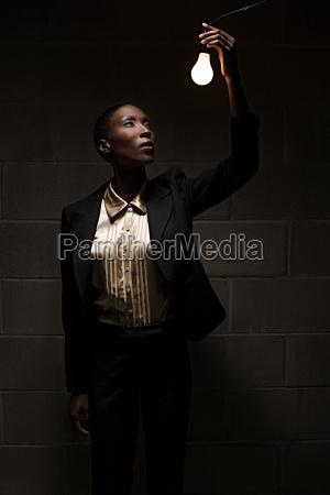 businesswoman holding lightbulb