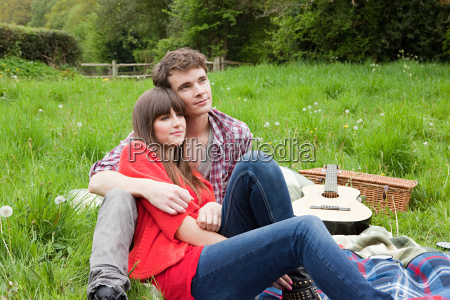 young couple on blanket in field