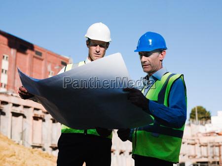 mature men inspecting blueprints on construction