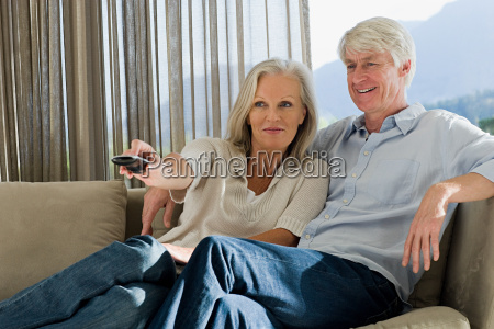 middle aged couple sitting on couch
