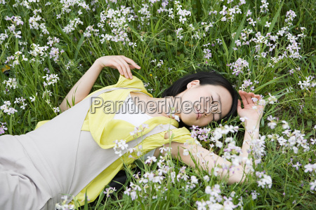 young woman lying in field of
