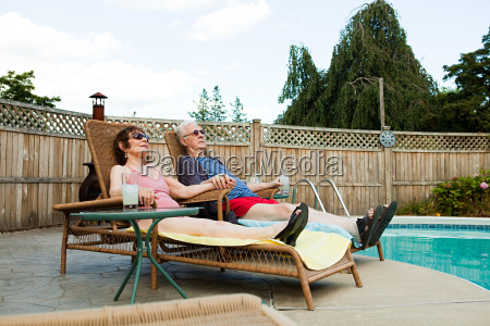 senior couple relaxing by swimming pool