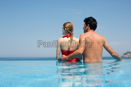 young couple in swimming pool looking
