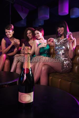four young women enjoying champagne in