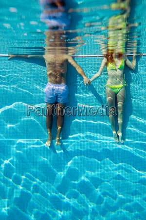 young couple holding hands in swimming