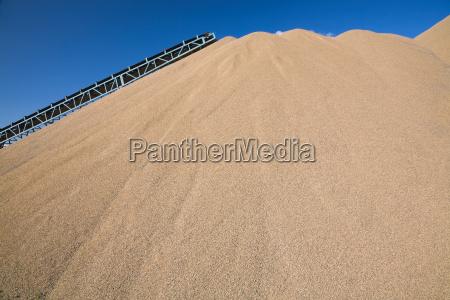 correia transportadora sobre monte de areia