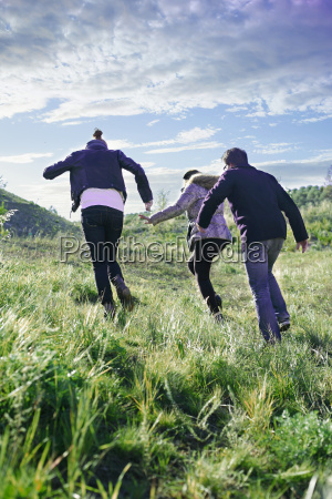 three young adult friends running up