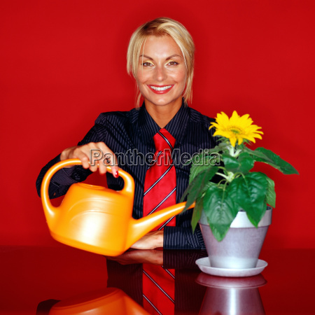 attractive woman watering a flower