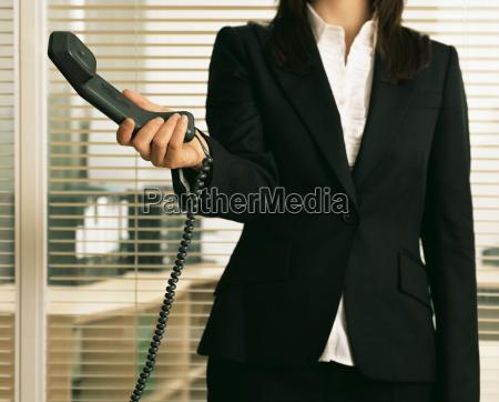 businesswoman holding a telephone handset