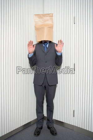 businessman with paper bag on head