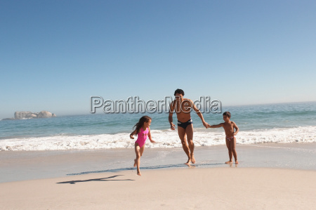 father and children running on a