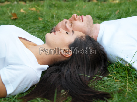 young couple relaxing in field