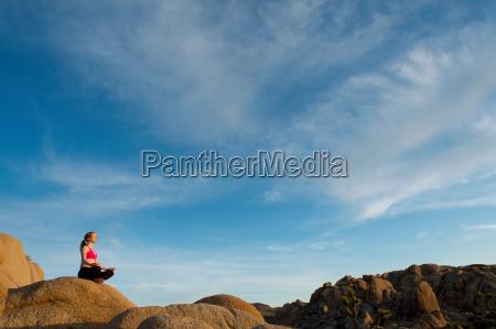 woman meditating on desert rocks