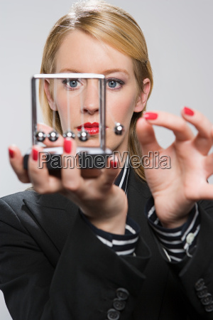 businesswoman holding a newtons cradle