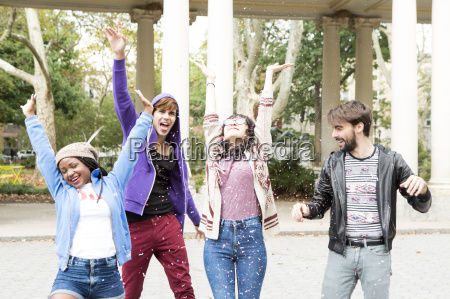 four young adult friends throwing confetti