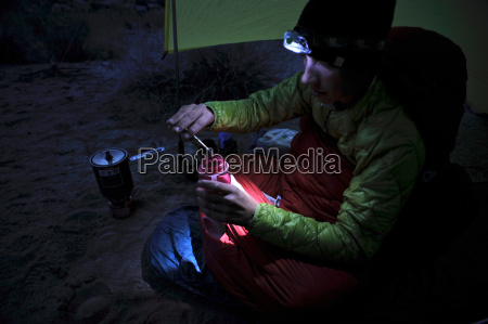 hiker having meal at camp in