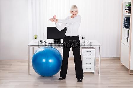 empresaria fazendo exercicio no escritorio