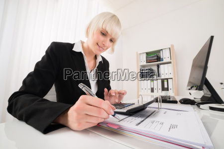 businesswoman calculating invoice in office