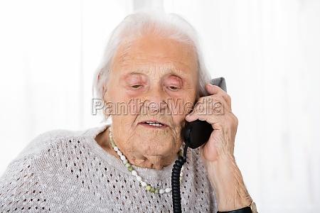 mulher senior que fala no telefone