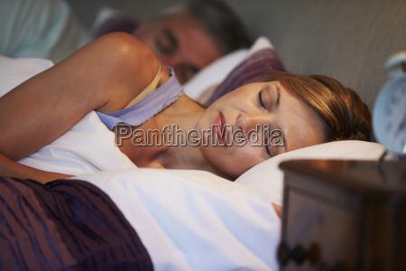 pares envelhecidos medios adormecidos na cama