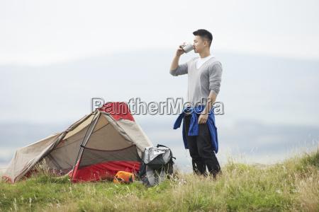 jovem em viagem de acampamento no