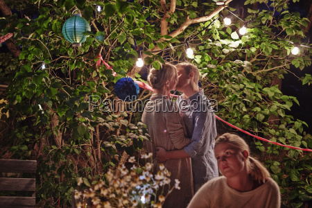 young couple embracing at garden party