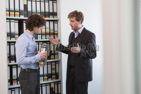 businessmen holding file in office storeroom