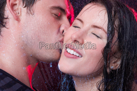 young couple kissing in the rain