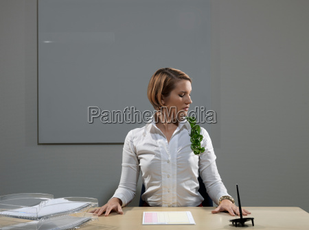 woman by desk with plant on