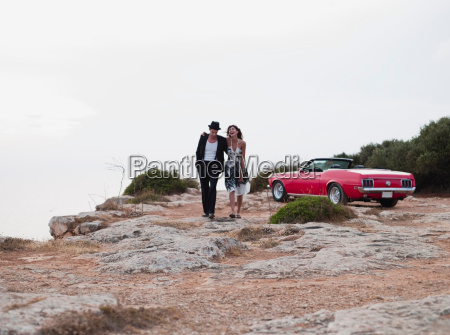 couple walking away from cabriolet