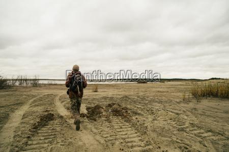 young man hiking walking beside lake