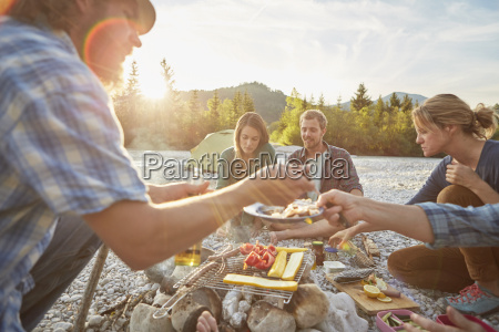 adults sitting around campfire serving food